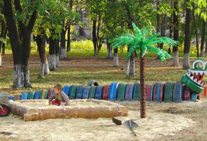яркая детская песочница в саду ручной сборки