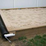 светлая песочница в саду из подручных средств