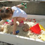 яркая песочница в саду ручной сборки